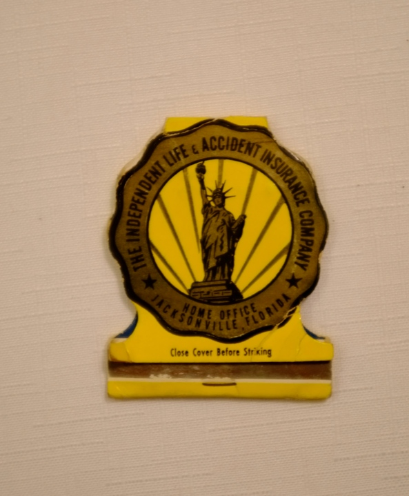 Paper matchbook with scalloped edges, yellow with gold and black Statue of Liberty in center with gold surround of Independent Life Insurance Company.