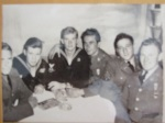 Charles HOPKINS sitting at table with other uniformed men, one other in Navy and 4 in another uniform.  Charles HOPKINS is in the middle with a man's arm around him.