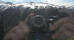 Snow capped mt with reflection of hands holding camera