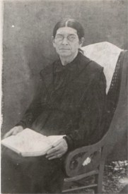 Leitha DICKERSON HOLDER in rocker, book in hand, glasses on